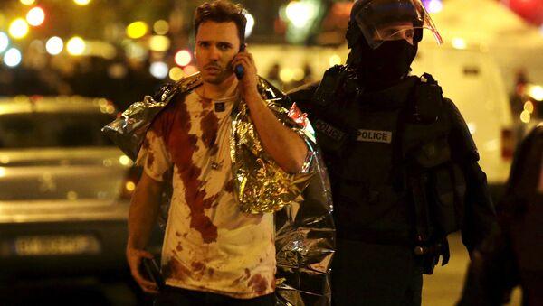 Francuski policajac pomaže jednoj od žrtava koja je umazana krvlju u blizini pozorišta Bataklan, Pariz - Sputnik Srbija