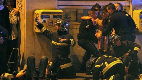 Francuski vatrogasci pomažu povređenom momku u blizini Bataklan koncertne dvorane nakon pucnjave u Parizu, Francuska, 13. novembra 2015 - Sputnik Srbija