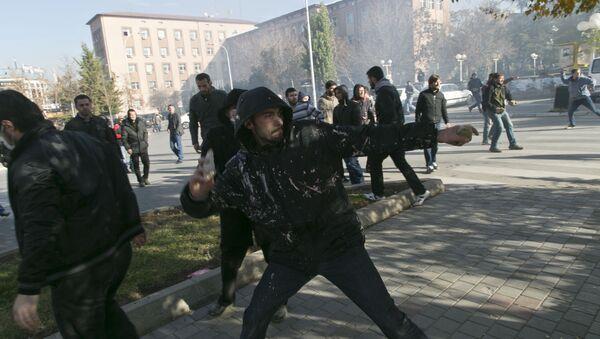 Pristalica opozicionih stranaka na Kosovu baca kamen ka policiji na demonstracijama u Prištini - Sputnik Srbija