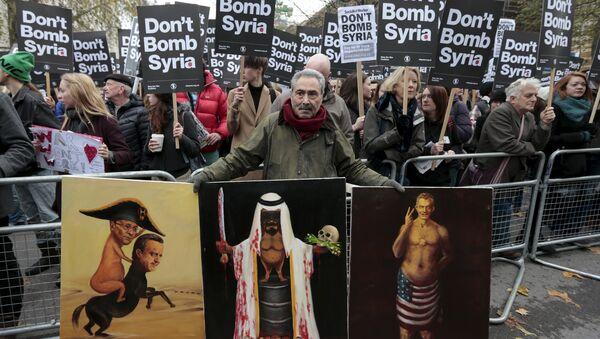 Umetnik Kaja Mar pokazuje politički inspirisane slike na protestu protiv vojne akcije protiv ID u Siriji, održanom ispred Dauning strita u Londonu, 28. novembra 2015. - Sputnik Srbija