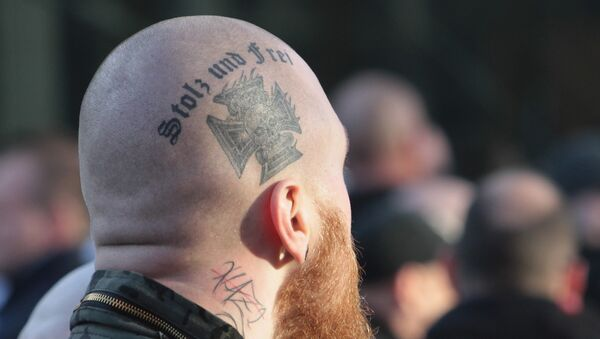 Припадник деснице на протесту са тетоважом Поносан и слободан. - Sputnik Србија