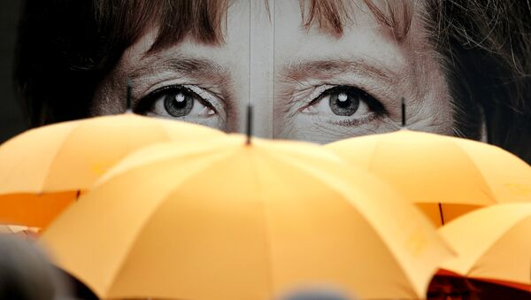 Supporters of the Christian Democratic Union (CDU) hold umbrellas in front of a giant portrait of German Chancellor Angela Merkel during an election campaign event in front of the party's headquarter in Berlin, Germany, Monday, Sept. 16, 2013. - Sputnik Srbija
