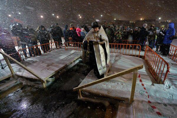 Sveštenik osvećuje ledenu rupu u Vladivostoku. - Sputnik Srbija