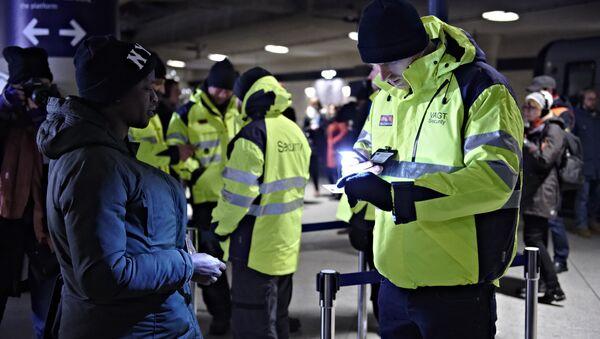 Policajac proverava pasoš putnice na železničkoj stanici međunarodnog aerodroma u Kopenhagenu, Danska, da bi sprečio ulaz izbeglica u Švedsku. - Sputnik Srbija