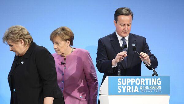 Британски премијер Дејвид Камерун за говорницом а иза њега је немачка канцеларка Ангела Меркел - Sputnik Србија