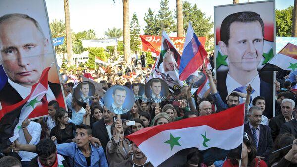 Присталице Асада са руским затставама и траснпаретном са ликом Владимира Путина, у граду Тарутус, Сирија - Sputnik Србија