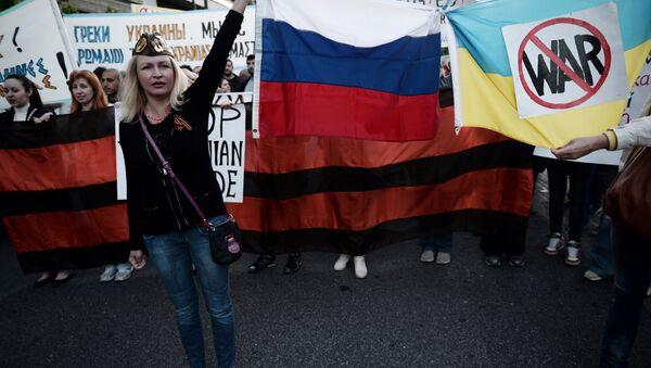 Ljudi drže ruske i ukrajinske zastave povezane i šalju anti-ratne poruke - Sputnik Srbija