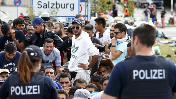 Немачки полицајци стоје испред миграната који чекају да пређу границу из Аустрије у Немачку, Немачка - Sputnik Србија