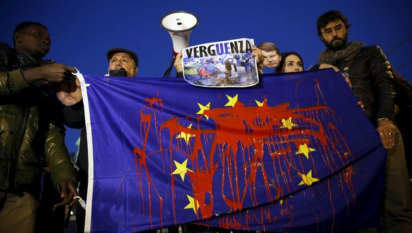 Демонстранти држе заставу Европске уније умрљану фарбом и учествују у протесту против европске политике за избеглице у Мадриду 11. март 2016. године - Sputnik Србија