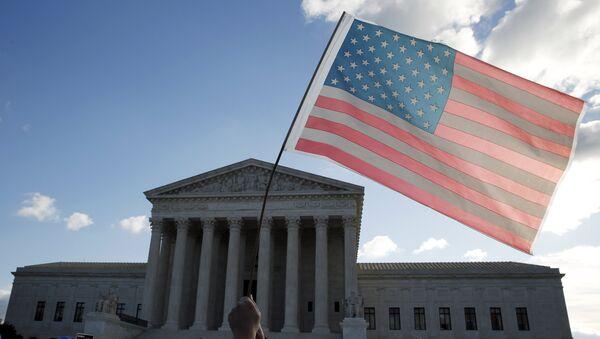 Демонстрант држи  америчку заставу испред  Врховног суда у Вашингтону - Sputnik Србија