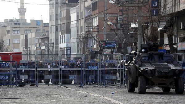 Људи иза зида који чува полиција у Турском граду Дијарбакир дана 16. марта - Sputnik Србија