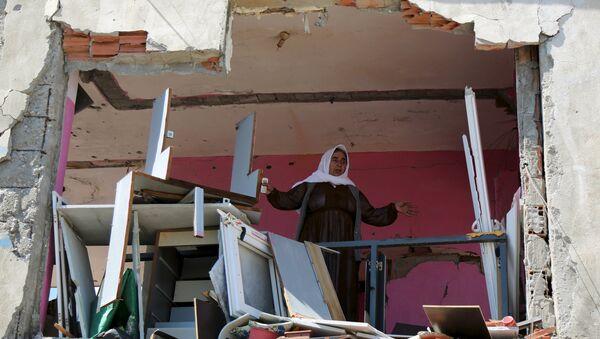 Жена стоји у њеној кући, која је оштећена током сукоба између турских снага безбедности и курдских милитаната, у југоисточном граду Идил - Sputnik Србија