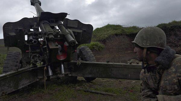 Jermenski vojnik samoodbrane Nagorno-Karabaha stoji ispred topa u gradu Madagis gde su eskalirali sukobi sa Azerbejdžancima. - Sputnik Srbija