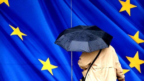Жена са кишобраном поред заставе ЕУ - Sputnik Србија