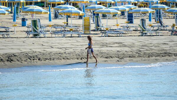 Žena šeta plažom u blizini Rima - Sputnik Srbija