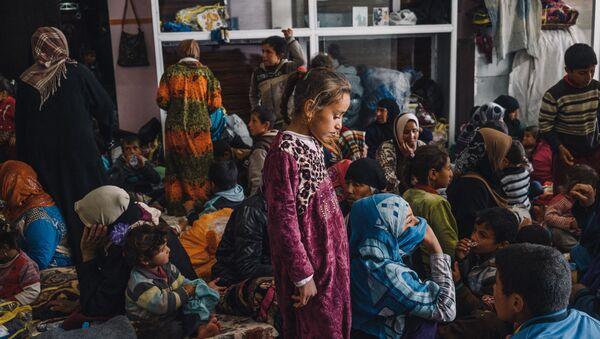 Девојчица стоји међу женама и децом у згради која служи као склониште за цивиле у Махмуру источно од Мосула у Ираку - Sputnik Србија