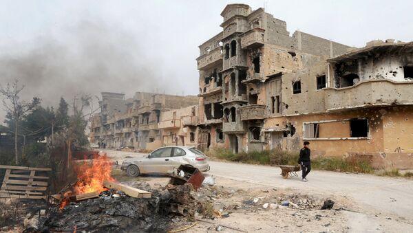 Човек вуче колица поред кућа уништених у борбама између снага оданих либијској власти и исламиста у Бенгазију (Либија) - Sputnik Србија
