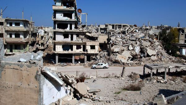 In this picture taken Friday, Feb. 26, 2016, a car drives through a devastated part of the old city of Homs, Syria - Sputnik Srbija