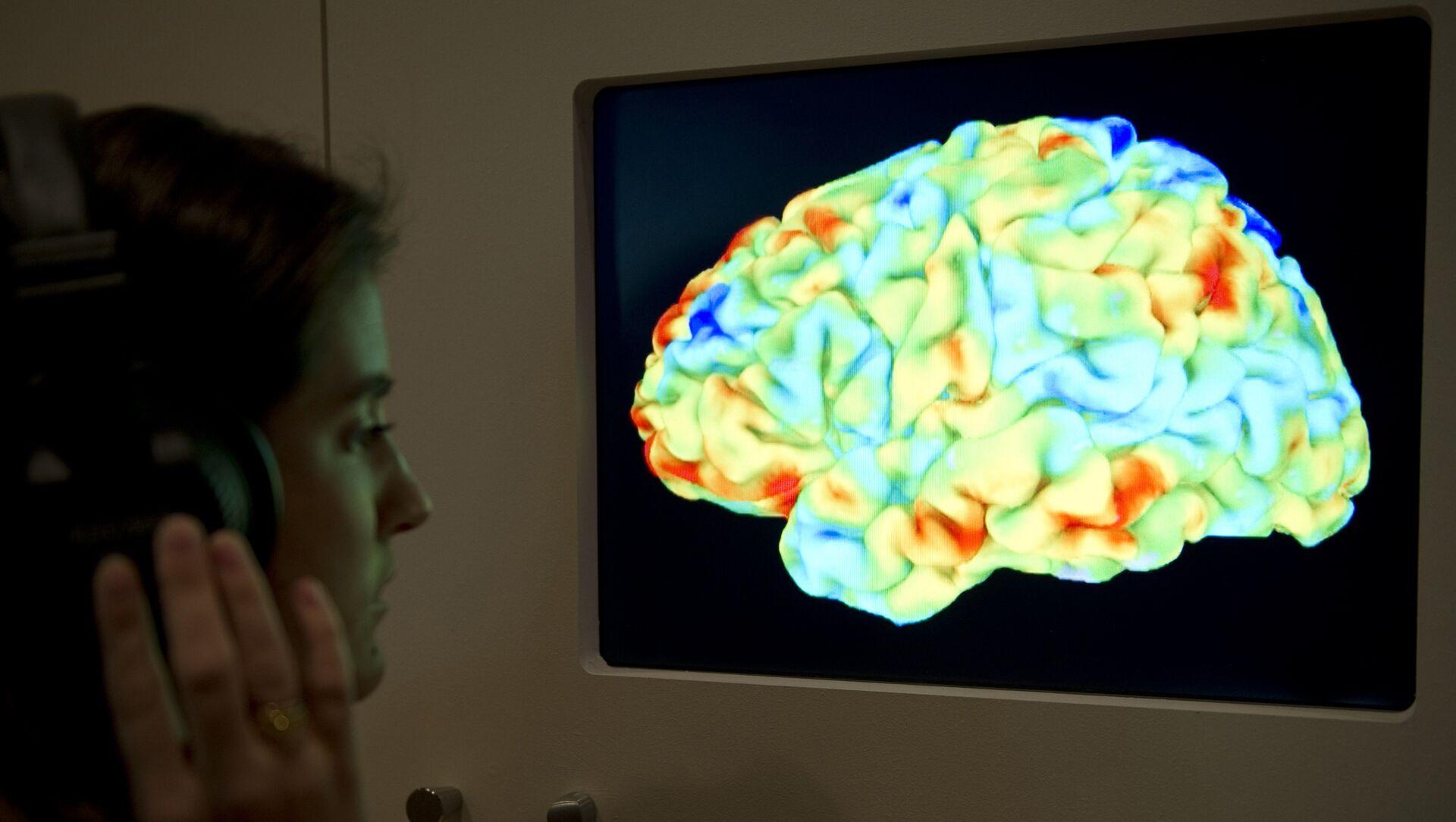 Žena posmatra funkcionalnu sliku magnetne rezonance koji pokazuje delove ljudskog mozga - Sputnik Srbija, 1920, 12.02.2021