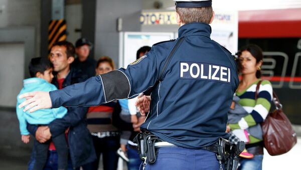 Полицајац усмерава мигранте на железничкој станици у Минхену. - Sputnik Србија