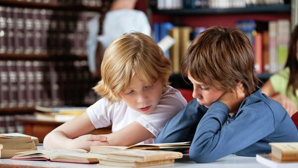 Дечаци читају књигу у библиотеци - Sputnik Србија