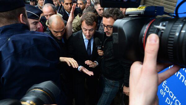 Француски министар економије Емануел Макрон пролази између демонстраната док долази на представљање нове маркице у Пошти Француске у Монтреју - Sputnik Србија