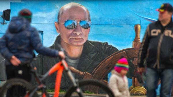 Пешаци пролазе поред портрета руског председника Владимира Путина на зиду у Јалти - Sputnik Србија