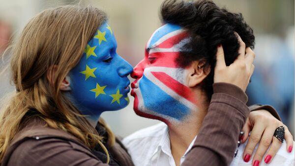 Dvoje aktivista ofarbanih lica bojama zastave EU i Velike Britanije ljube se ispred Branderbuške kapije u Berlinu. - Sputnik Srbija