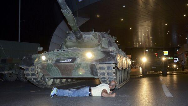 Човек лежи испред тенка турске војске на аеродрому Ататурк у Истанбулу - Sputnik Србија