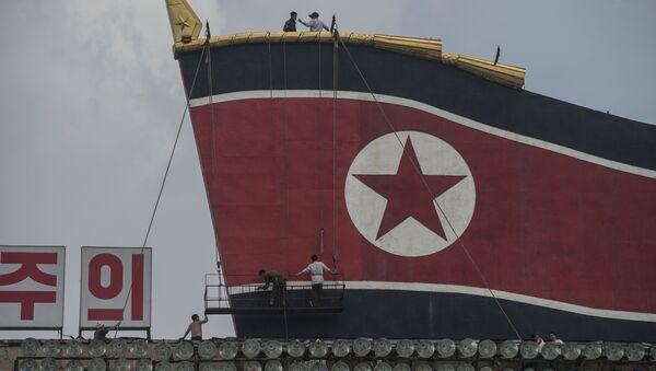 Radnici slikaju zastavu Severne Koreje na zgradi na Trgu Kim Il Sunga. - Sputnik Srbija