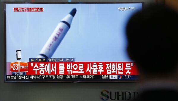 Јужнокорејанац у Сеулу гледа снимак лансирања ракете у Северној Кореји. - Sputnik Србија