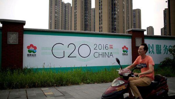 Čovek na motociklu prolazi pored bilborda za samit G20 u kineskom gradu Hangžu - Sputnik Srbija