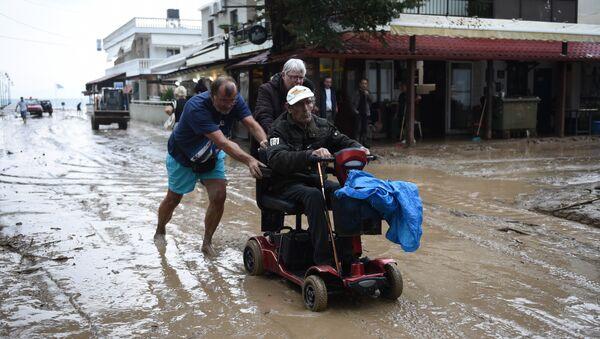 Људи се пробијају кроз поплављену улицу у селу Аја Тријада 20 километара од Солуна. - Sputnik Србија