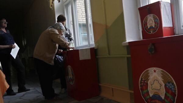 Žena ubacuje listić u glasačku kutiju tokom parlamentarnih izbora u Minsku u Belorusiji. - Sputnik Srbija