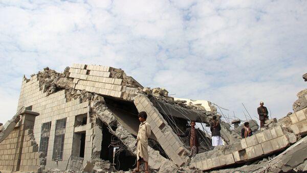 Људи стоје на рушевинама школе коју су бомбардовали Саудијци у северозападном јеменском граду Сада - Sputnik Србија