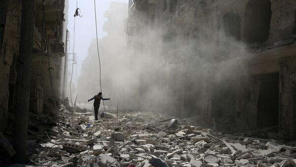 Čovek se probija kroz ruševine zgrade nakon vazdušnog napada na deo Alepa - Sputnik Srbija