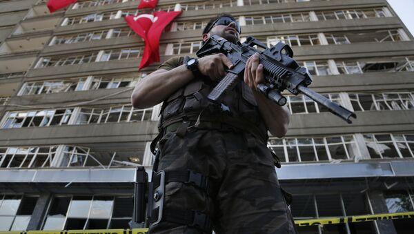 Припадник специјалних снага полиције Турске стражари испред оштећене зграде полиције у Анкари - Sputnik Србија