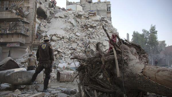 Члан Сиријске цивилне заштите, познате и као Бели шлемови, стоји поред порушених зграда у Алепу - Sputnik Србија