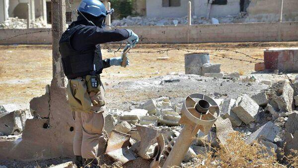Pripadnik istražnog tima UN uzima uzorke peska u blizini jedne od hemijskih raketa koja je ispaljena u Damasku - Sputnik Srbija