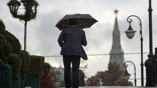 Мушкарац шета по киши у Москви - Sputnik Србија
