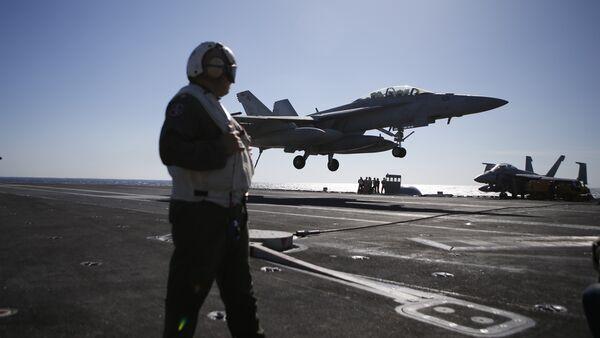Припадник америчког ваздухопловства посматра слетање авиона Ф/А-18 Хорнет на носач авиона Роналд Реган - Sputnik Србија