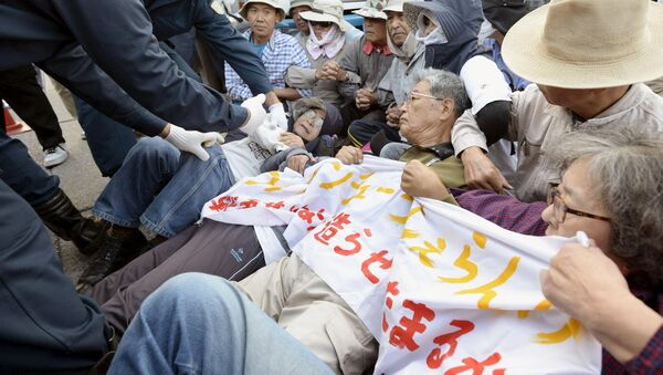 Protesters lie on the ground as they try to block work on a contentious U.S. air base in front of the gate of the U.S. Marine Corps Camp Schwab in Nago on the southern Japanese island of Okinawa - Sputnik Србија
