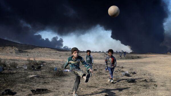 Деца играју фудбал у близини нафтних поља које је спалио ДАЕШ, јужно од Мосула - Sputnik Србија