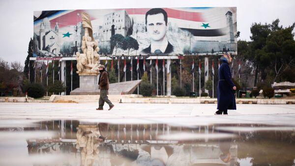 Људи пролазе поред билборда са ликом сиријског председника Башара Асада у Алепу - Sputnik Србија