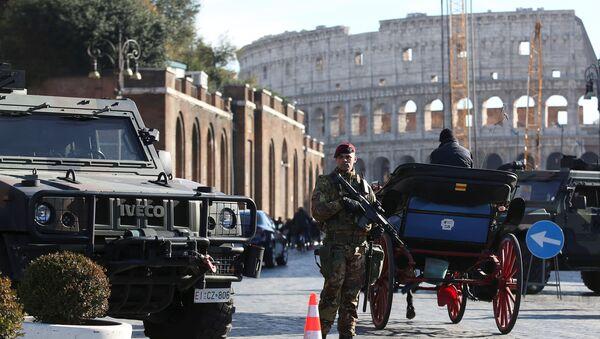 Naoružani pripadnik vojske Italije patrolira ispred Koloseuma dok su u Rimu uvedene pojačane bezbednosne mere pred proslavu Nove godine - Sputnik Srbija