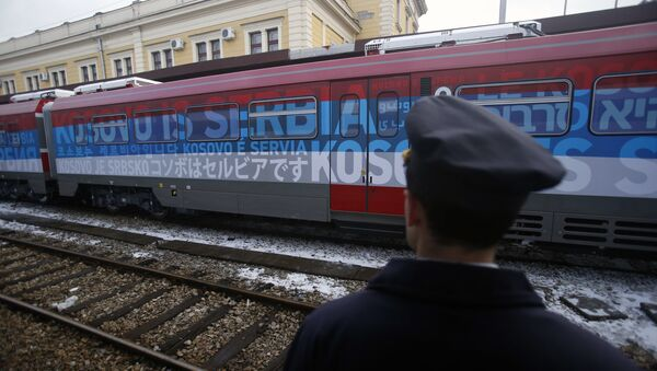Железничар стоји поред воза који саобраћа на линији Београд-Косовска Митровица - Sputnik Србија