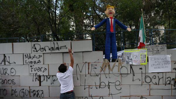 Demonstrant ispisuje grafit na simboličnom zidu ispred američke ambasade u Meksiko Sitiju - Sputnik Srbija