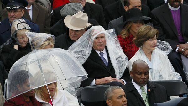 Бивши амерички председник Џорџ В. Буш штити се кабаницом од кише на церемонији инаугурације Доналда Трампа у Вашингтону - Sputnik Србија