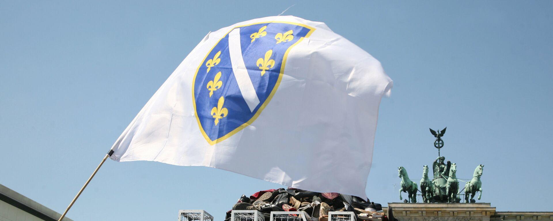 Zastava Bosne i Hercegovine ispred gomile cipela i logoa UN ispred Brandenburške kapije u Berlinu. - Sputnik Srbija, 1920, 21.07.2021