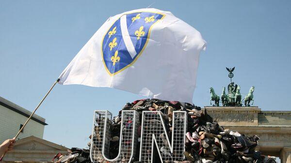 Zastava Bosne i Hercegovine ispred gomile cipela i logoa UN ispred Brandenburške kapije u Berlinu. - Sputnik Srbija